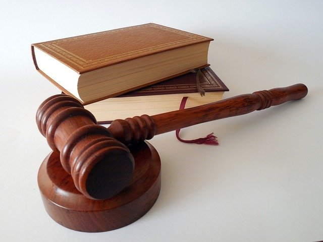 two law books and a wooden gavel. getting the C-23 license requires that you do live scan fingerprinting
