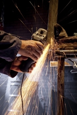 metal worker using a machine to cut a large piece of metal, sparks flying