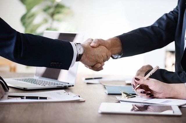 Two business men shaking hands. Building permit services are a vital tool for general contractors to scale their businesses