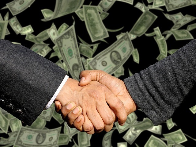Two people shaking hands with dollars in the background. The CSLB requires home improvement sales person to be registered with the state of california