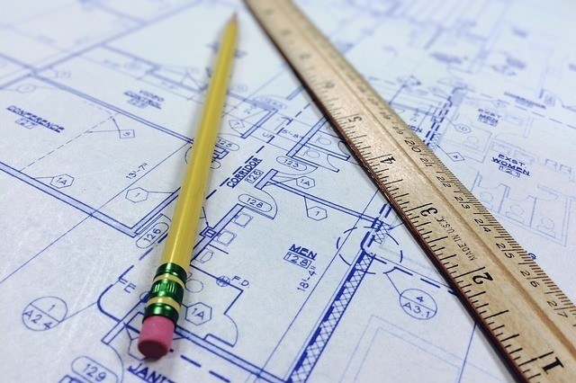 a pencil and wooden ruler laying on top of some construction plans. a foreman should have core skills including, blueprint reading and math