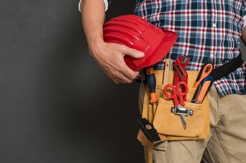 A contractor with a gold tool belt holding a red hard hat. Journeyman level tradesman can earn substantial income