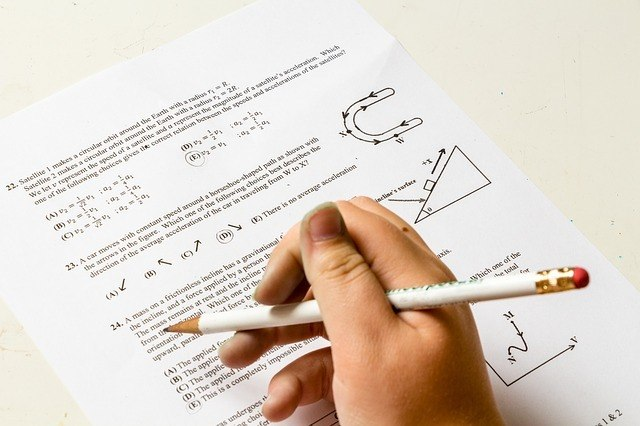 a person holding a white pencil above an exam