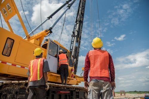 two construction contractors looking at a large industrial drill
