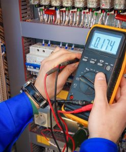 Electrical Engineer adjusts electrical equipment with a multimeter in his hand closeup. Professional electrician in electric automation cabinet. electrical contractors in Colorado must meet state requirements